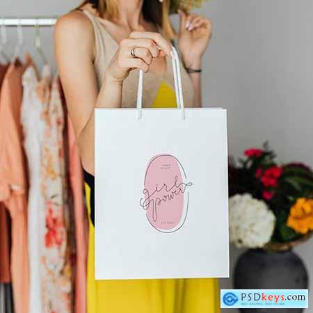 Woman carrying a shopping paper bag mockup 1208072