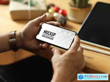 Hand holding smartphone mockup and christmas decorations